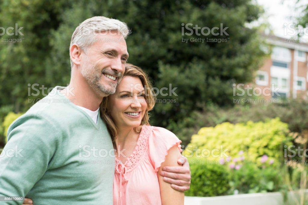 Reifer Mann mit Arm um Frau und sah lächelnd entfernt – Foto