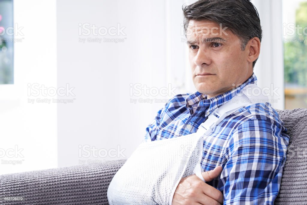 Mature Man With Arm In Sling At Home stock photo