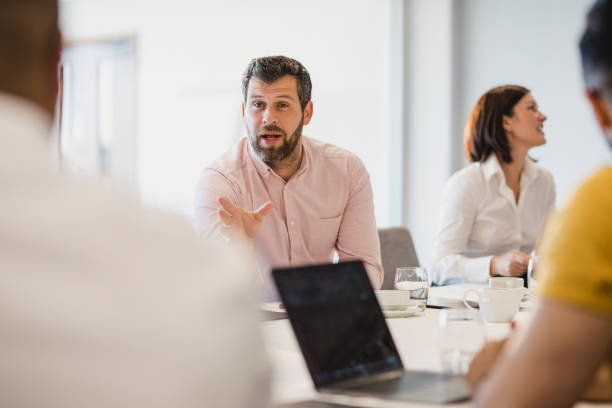 Mature man with beard talking to colleagues at conference table stock photo