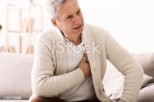 Mature man with chest pain, suffering from heart attack at home