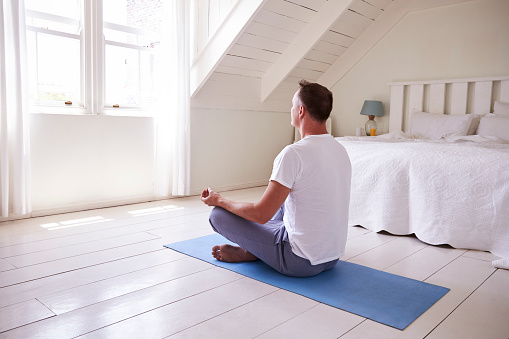 Mature Man With Digital Tablet Using Meditation App In Bedroom Stock Photo - Download Image Now