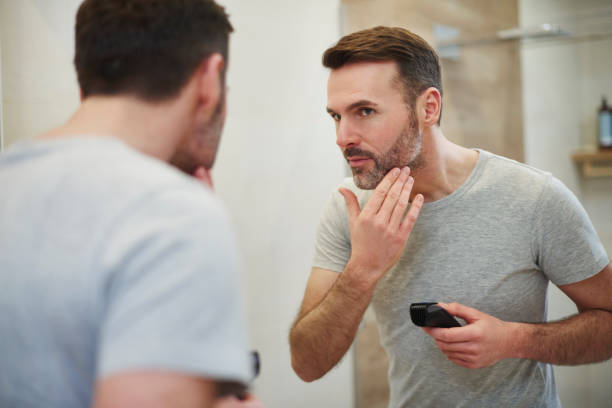 Mature man with electric razor shaving Mature man with electric razor shaving hair stubble stock pictures, royalty-free photos & images