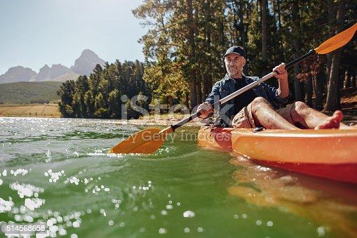 Portrait of a mature man with enjoying kayaking in a lake. Caucasian man wearing a cap paddling a kayak on summer day.