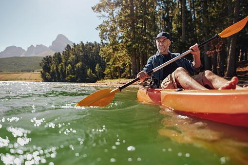 Mature man with enjoying kayaking in a lake