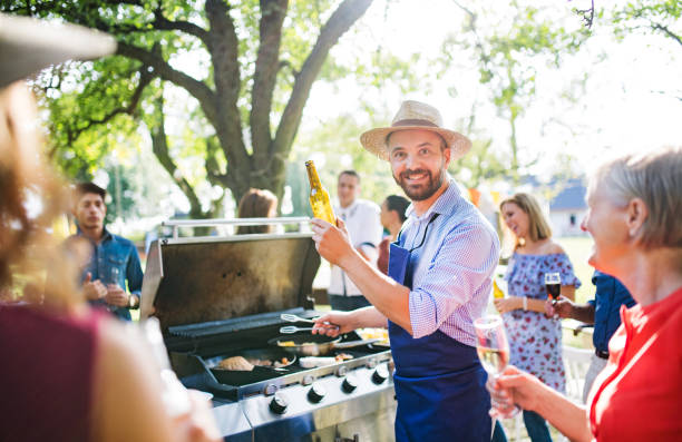 A mature man with family and friends cooking and serving food on a barbecue party. stock photo