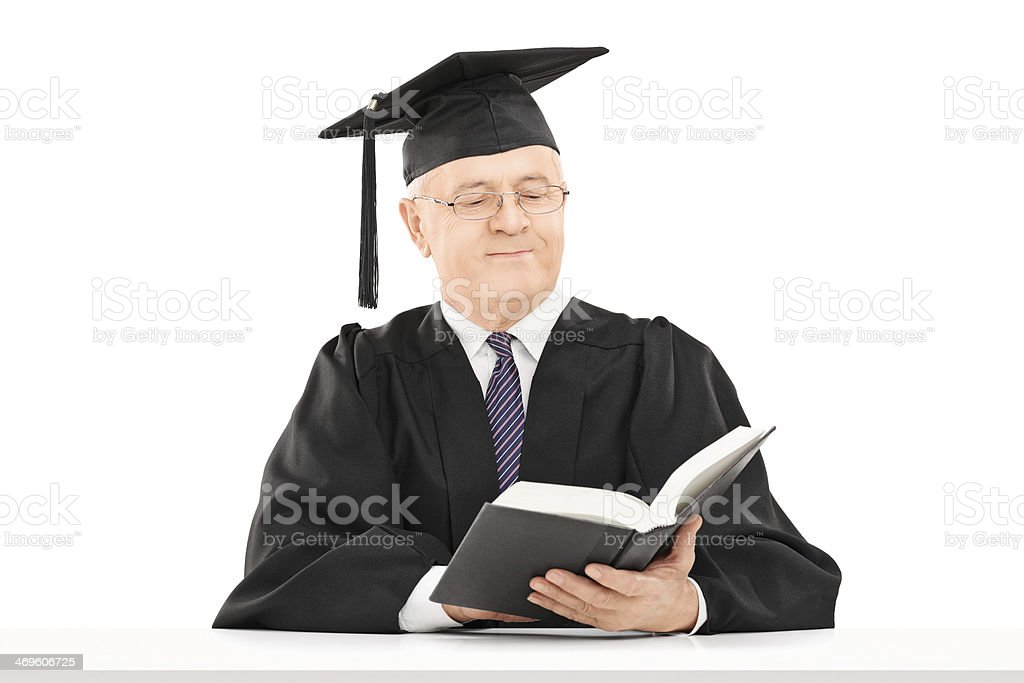 Mature man with graduation hat reading book seated on table stock photo