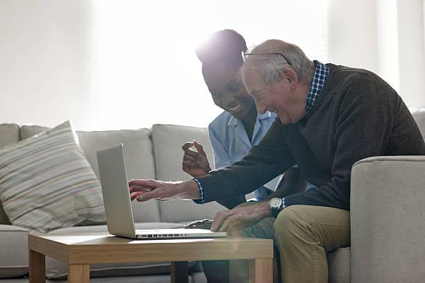 reifer mann mit seinem krankenschwester blick auf den laptop - heimerziehung stock-fotos und bilder