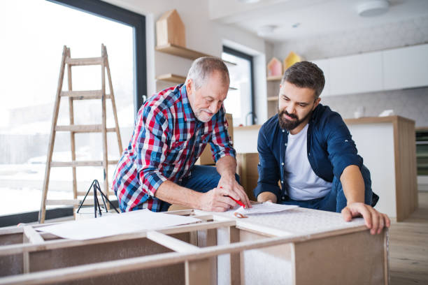 A mature man with his senior father assembling furniture, a new home concept. A hipster mature man with his senior father assembling furniture, a new home concept. home improvement stock pictures, royalty-free photos & images
