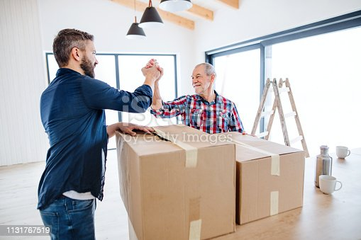 istock A mature man with his senior father furnishing new house, a new home concept. 1131767519
