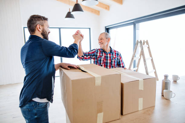 A mature man with his senior father furnishing new house, a new home concept. stock photo