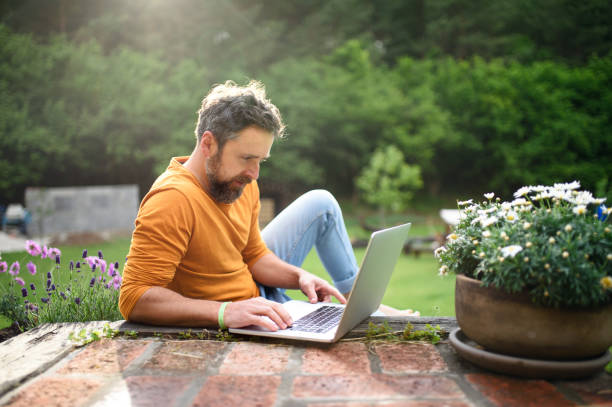 Mature man with laptop working outdoors in garden, home office concept. stock photo