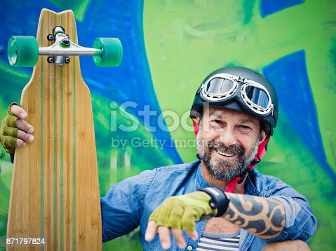 istock Mature man with longboard, graffiti on background 871797824