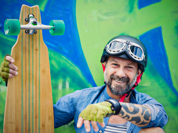 Mature man with longboard, graffiti on background Mature man with longboard, graffiti on background young at heart stock pictures, royalty-free photos & images