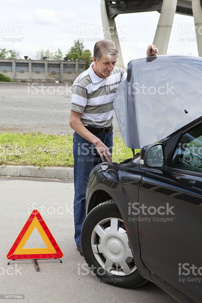 Mature man with opened car hood and emergency sign royalty-free stock photo
