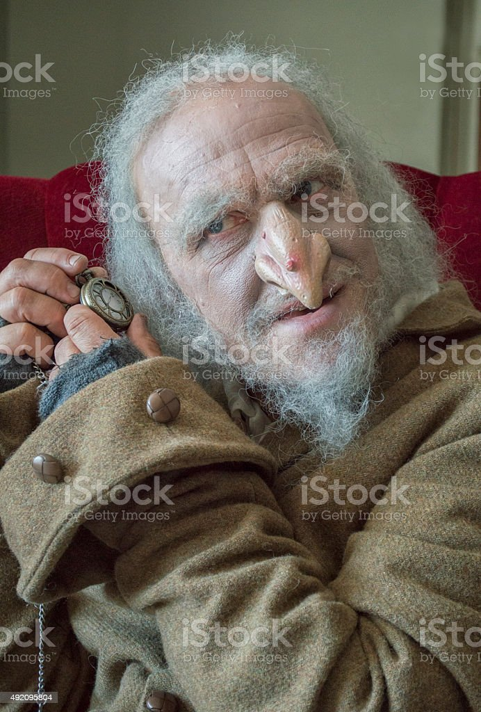 Mature man with scruffy appearance looking over pocket watch stock photo