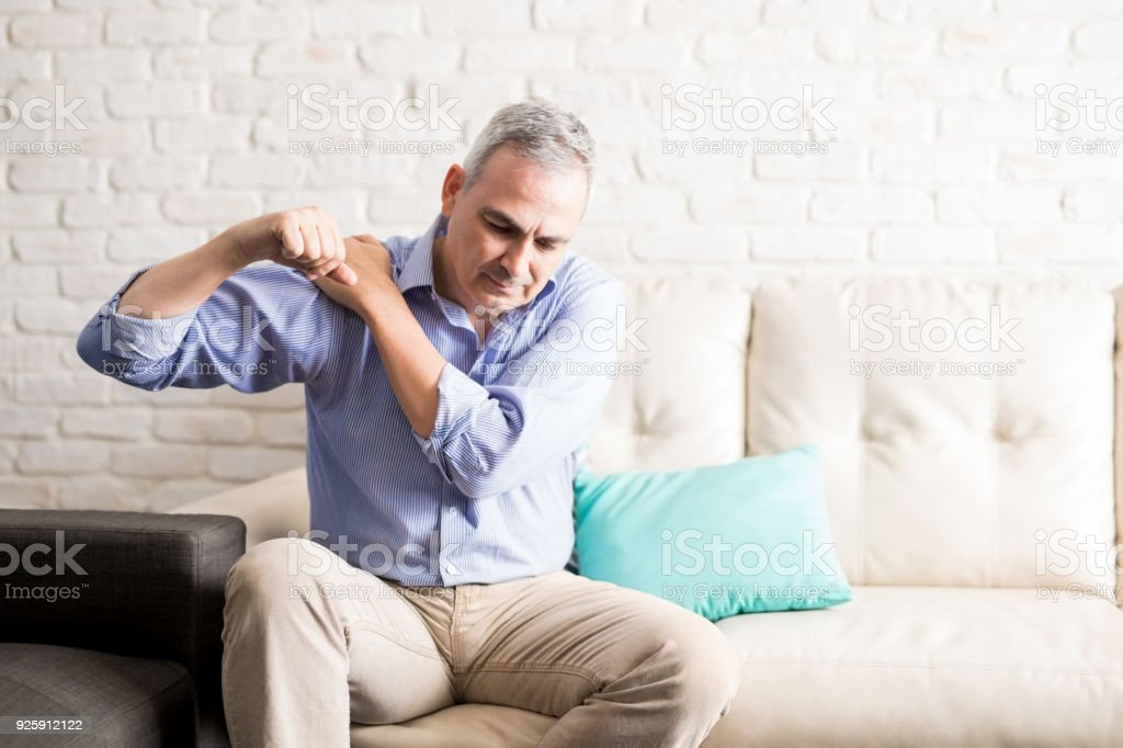 Mature man with shoulder pain at home royalty-free stock photo