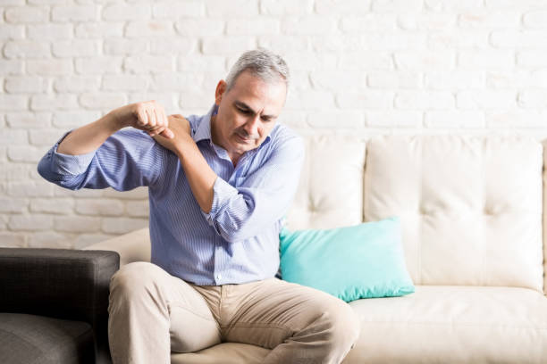 Mature man with shoulder pain at home stock photo