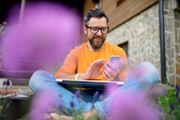 Mature man with smartphone working outdoors in garden, green home office concept. stock photo