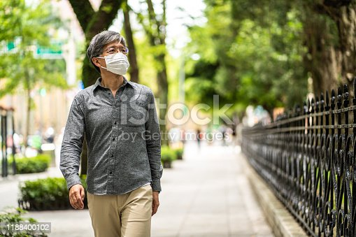 Mature gray-haired Taiwanese man with surgical mask walking on a sidewalk near public park