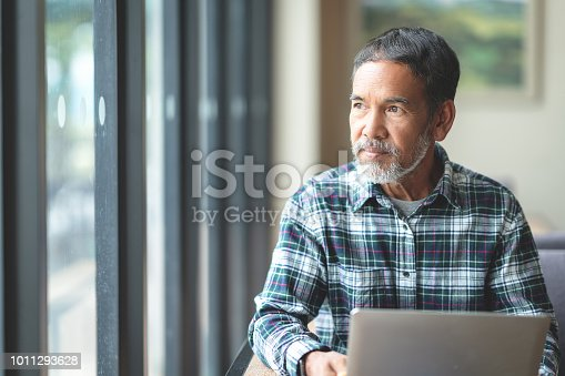 Mature man with white stylish short beard looking outside window. Casual lifestyle of retired hispanic people or adult asian man thinking and feeling confident sitting at modern coffee shop cafe.