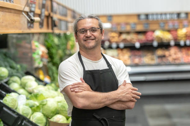 Mature man working at a supermarket vegetables and fruit section Hispanic Mature man working at a vegetables and fruit section grocer stock pictures, royalty-free photos & images