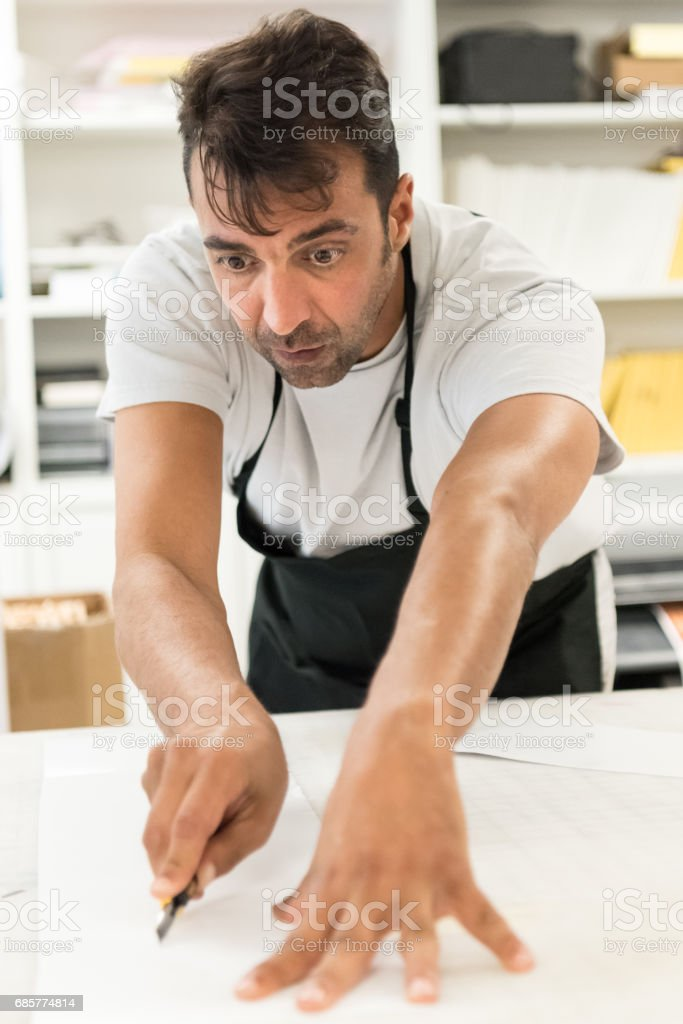 Mature man working at his graphic design-printing shop royalty-free stock photo