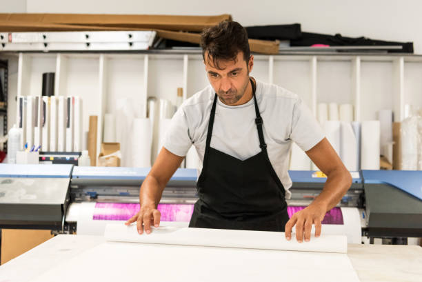 mature man working at his printing-graphic design shop - graphic print stock photos and pictures