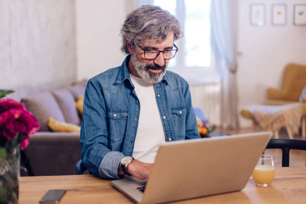 Mature man working from home during the COVID-19 lockdown stock photo