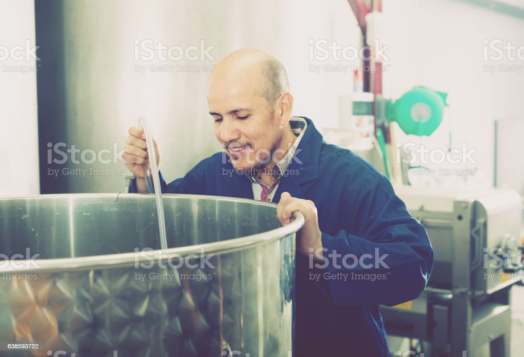 mature man working in wine fermentation section stock photo