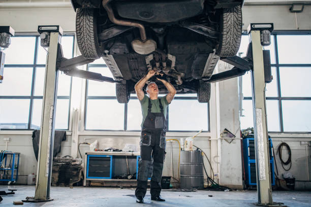 Mature man working on a vehicle in auto repair shop stock photo