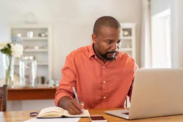 evde laptop çalışan olgun adam - konsantre olma stok fotoğraflar ve resimler