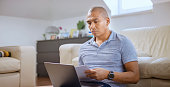 istock Mature man working on laptop in living room 1313799547
