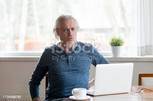 821012164istockphoto Mature man working on pc feels sudden back pain 1124436732