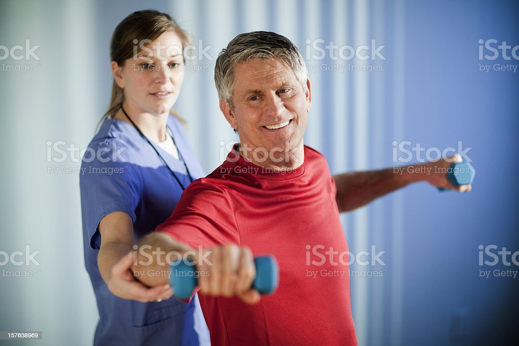 Hombre maduro trabajando con un fisioterapeuta - foto de stock