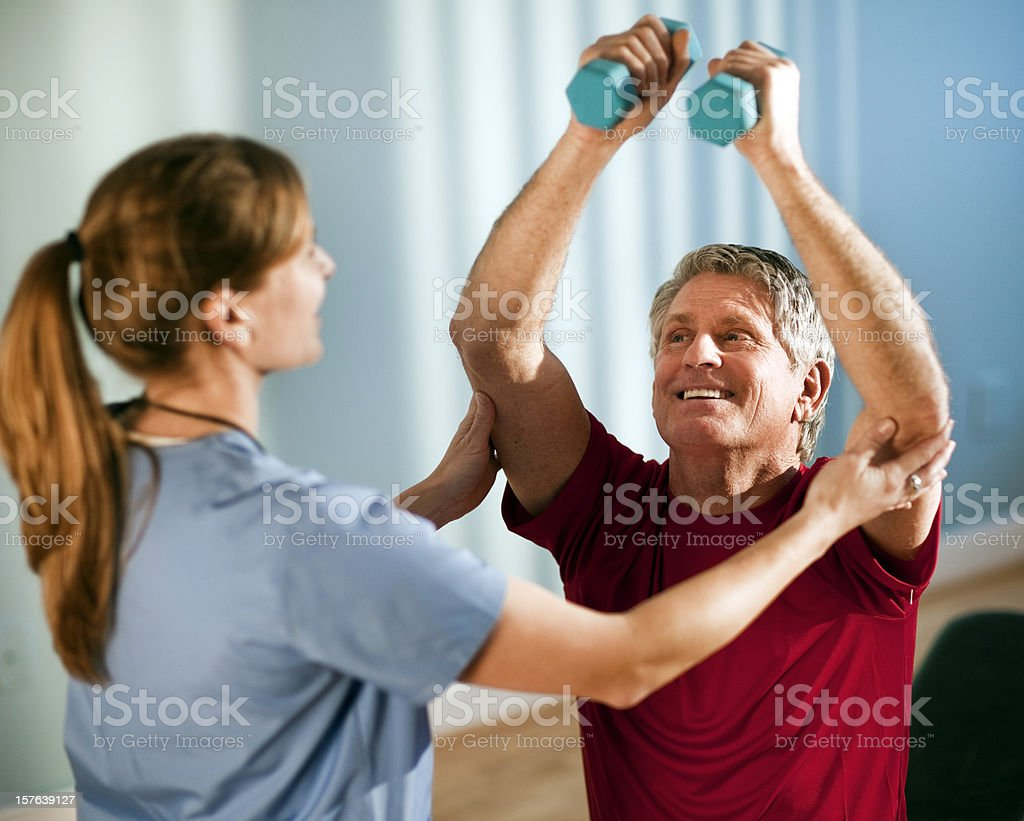 Mature Man Working With Female Physical Therapist royalty-free stock photo