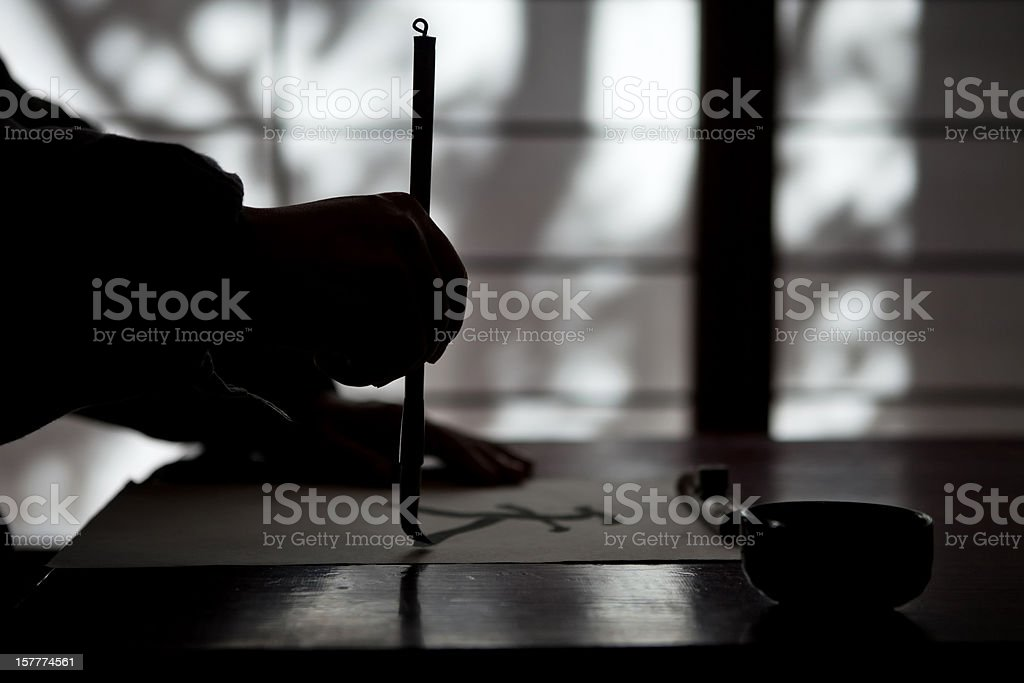 Mature man writing a calligraphic type royalty-free stock photo