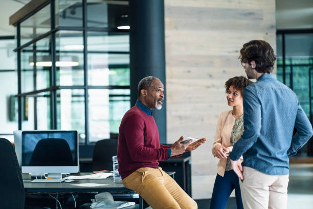 Mature manager discussing with young colleagues stock photo
