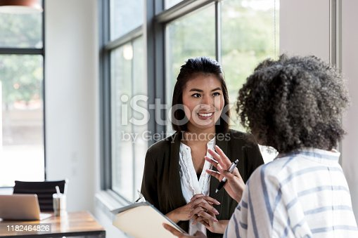 An unrecognizable mature adult female manager gives praise to a smiling mid adult female employee.