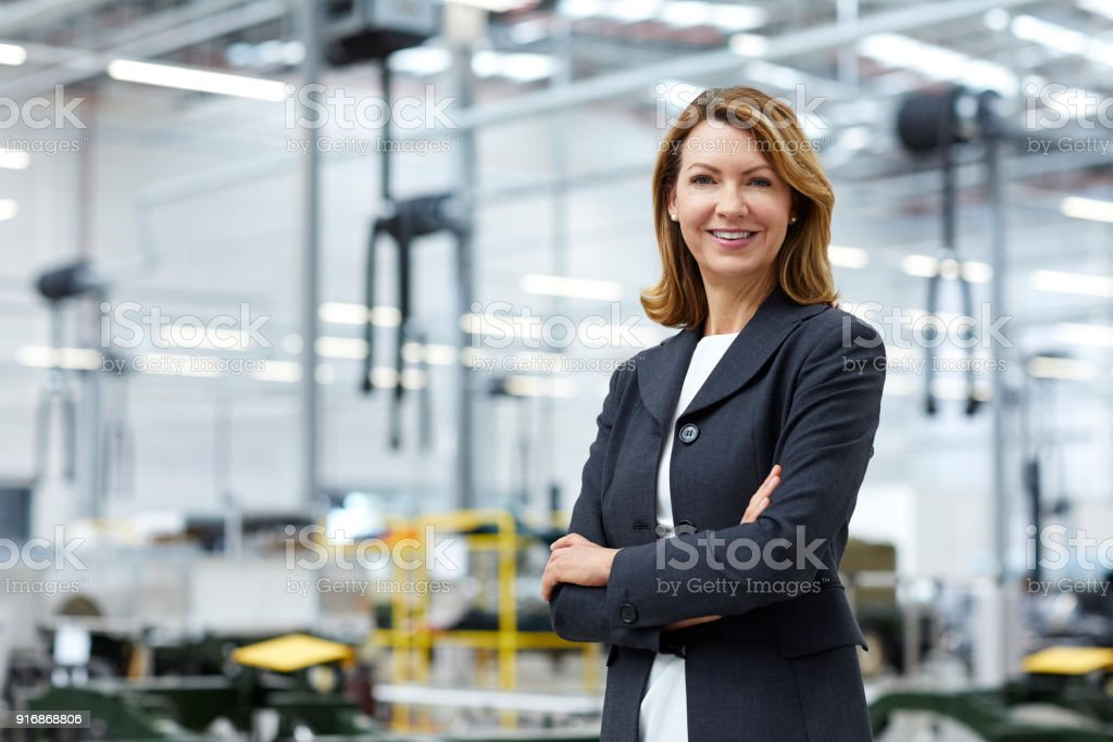 Portrait of mature manager with arms crossed in car plant. Confident...