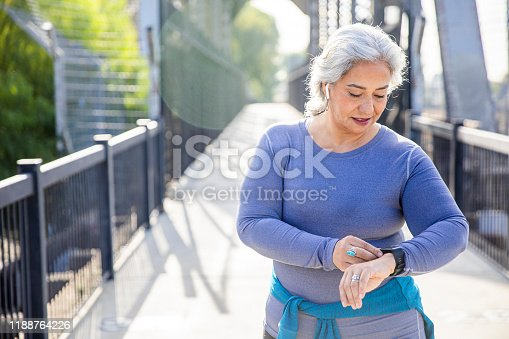 A mexican woman checking her fitness tracker