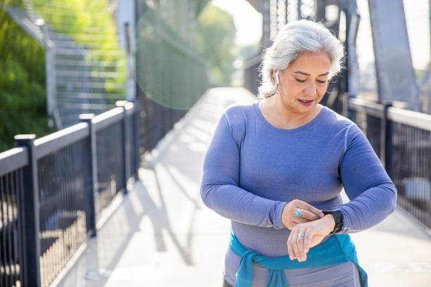 Mature Mexican Woman using fitness tracker A mexican woman checking her fitness tracker fitness tracker stock pictures, royalty-free photos & images