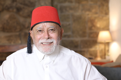 Mature middle Eastern man wearing classic fez hat.