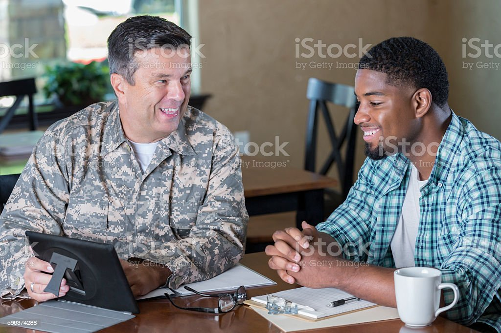 Mature military officer talking to man in recruitment office stock photo