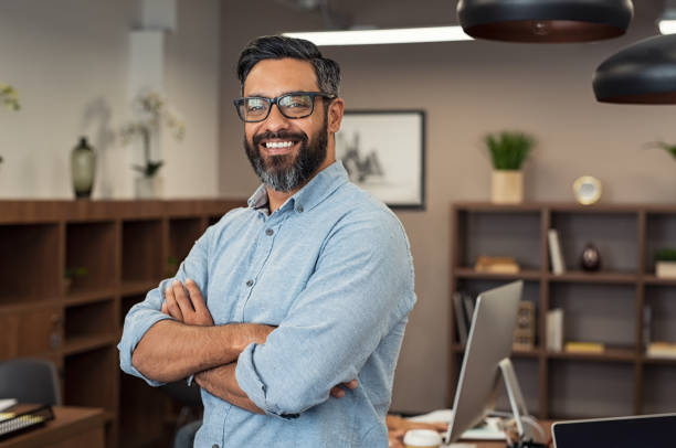 Mature mixed race business man Portrait of happy mature businessman wearing spectacles and looking at camera. Multiethnic satisfied man with beard and eyeglasses feeling confident at office. Successful middle eastern business man smiling in a creative office. latin american and hispanic ethnicity stock pictures, royalty-free photos & images