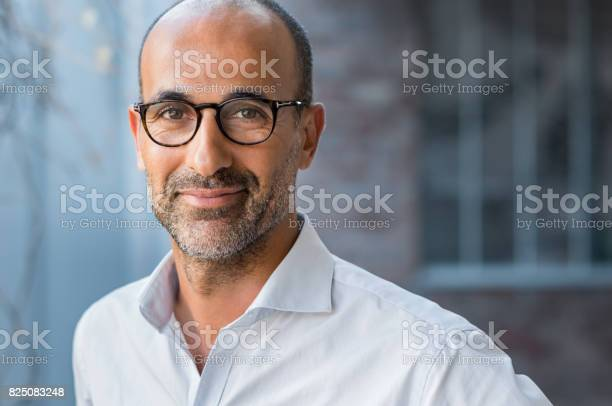 Portrait of happy mature man wearing spectacles and looking at camera outdoor. Man with beard and glasses feeling confident. Close up face of hispanic business man smiling.