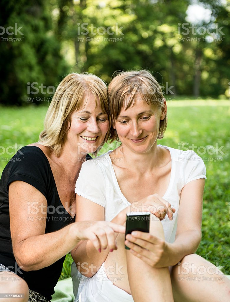 Mature mother and daughter with smartphone royalty-free stock photo