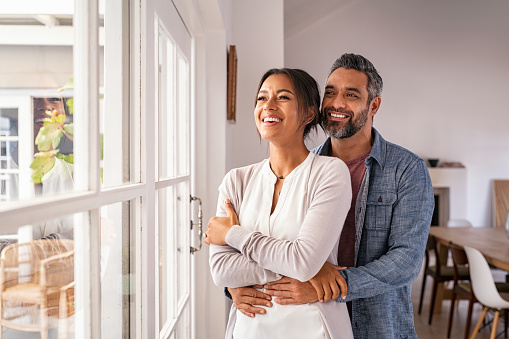 Smiling mid adult couple hugging each other and standing near window while looking outside. Happy and romantic mature man embracing hispanic wife from behind while standing at home with copy space. Future, vision and daydream concept.