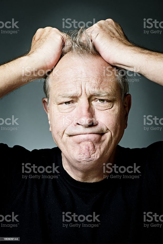 Mature old man frustrated pulling hair stock photo
