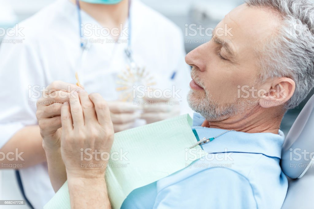 Mature patient looking at tooth sample while visiting dentist foto stock royalty-free