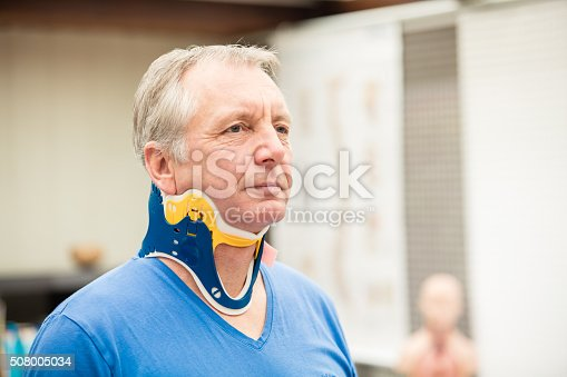 A mature patient wearing a spine collar. This brace gives shelter to the cervical spine after accident. XXXL size image.